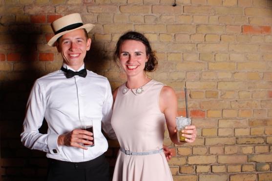 Elegantes Paar mit Drinks vor dem Photo Booth